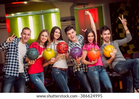 Cheerful friends at the bowling alley with the balls - stock photo