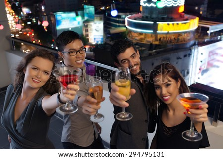 Cheerful friends at the rooftop party clinking glasses with you