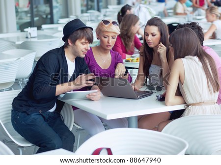 Cheerful friends browsing internet in a restaurant - stock photo