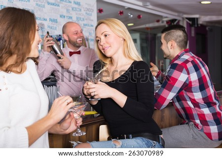 Cheerful friends drinking and chatting with happy barman at bar counter