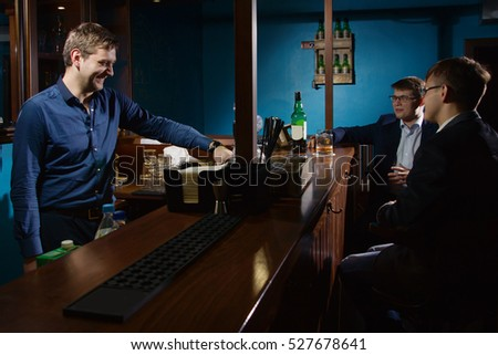 Cheerful friends drinking at bar counter in pub.