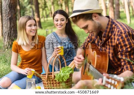 Cheerful friends enjoying nature and music - stock photo