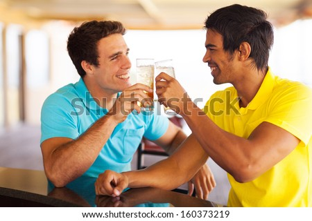 cheerful friends having beer at the pub, clinking glasses - stock photo