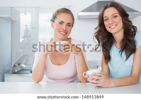 Cheerful friends having cup of coffee in the kitchen - stock photo