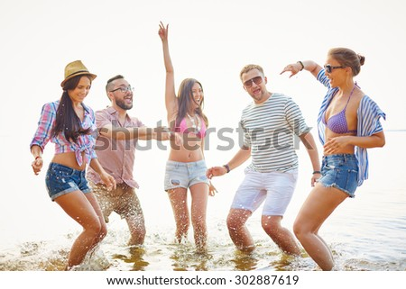 Cheerful friends having fun in water during vacations - stock photo