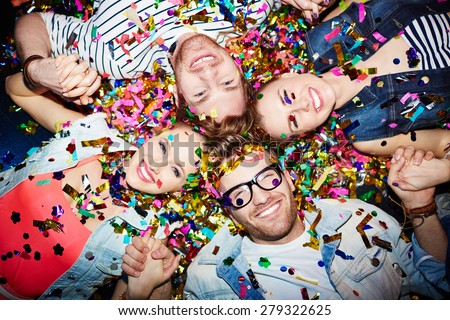 Cheerful friends lying on the floor in nightclub and looking at camera - stock photo