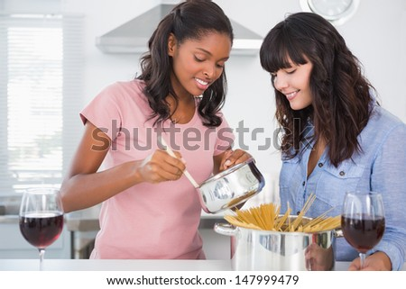 Cheerful friends preparing spaghetti dinner together at home in kitchen - stock photo