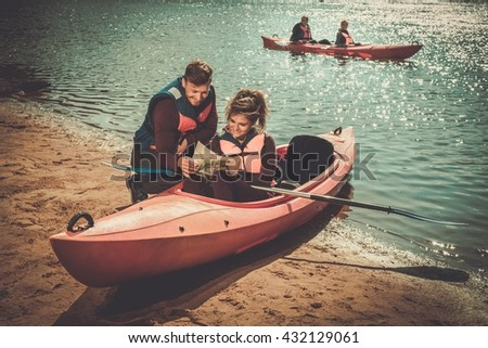 Cheerful friends reading a map in kayaks on a beach. - stock photo