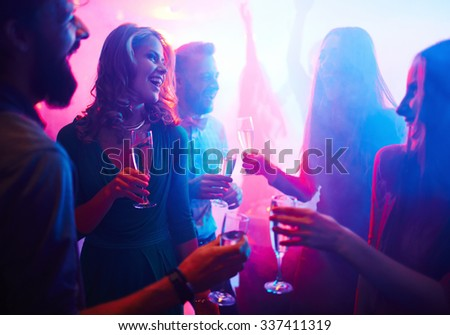 Cheerful friends with champagne spending time in night club