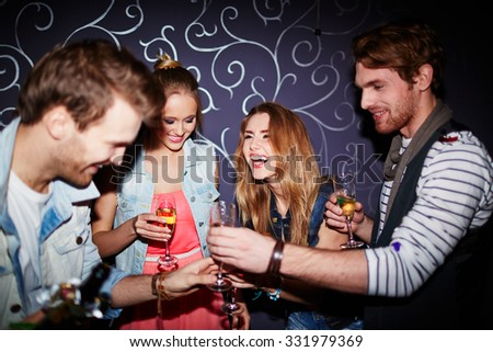 Cheerful friends with flutes of champagne spending time in nightclub - stock photo