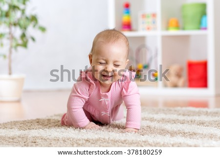 cheerful funny baby crawling indoors at home - stock photo