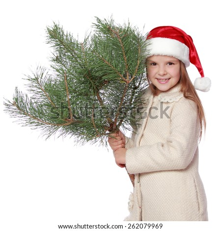 Cheerful funny little girl with blond hair in a red Santa hat holding a bush natural pine/Positive young girl in Santa's hat is happy and laughing with Christmas tree - stock photo