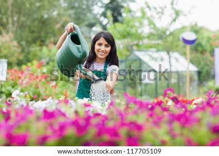 Cheerful gardener watering plants outside in garden center - stock photo