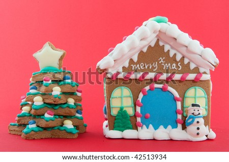 Cheerful gingerbread house and tree on a red background - stock photo