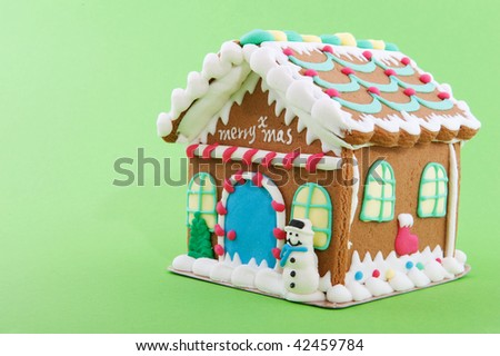 Cheerful gingerbread house on a green background - stock photo