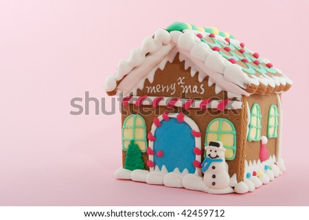 Cheerful gingerbread house on a pink background - stock photo
