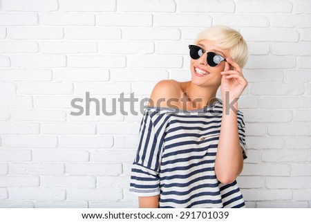 Cheerful girl adjusting her glasses and smiling - stock photo