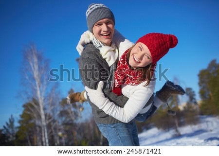 Cheerful girl and guy in knitted winterwear having fun in natural environment - stock photo