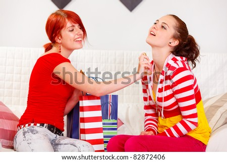 Cheerful girl applying new perfume on her girlfriend  at living room - stock photo