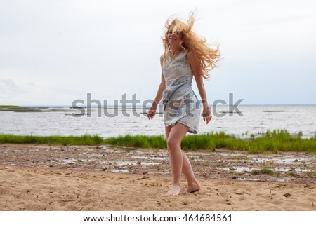 Cheerful girl. Beautiful girl. Happiness. Red-haired girl dancing on the sand. Freedom. Wind. Girl in a short dress. Success. Girl jumping on the beach. Wind waves hair