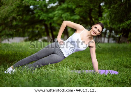 Cheerful girl doing exercise in the nature