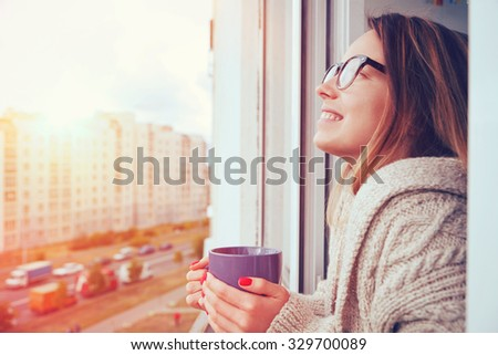 cheerful girl drinking coffee in morning sunlight in open window - stock photo