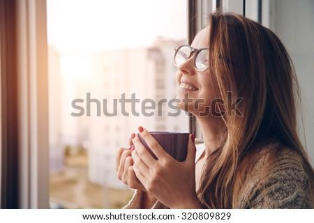 cheerful girl drinking coffee or tea in morning sunlight - stock photo