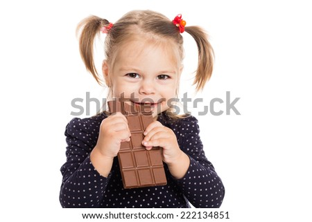 Cheerful girl eating chocolate. Two years. - stock photo