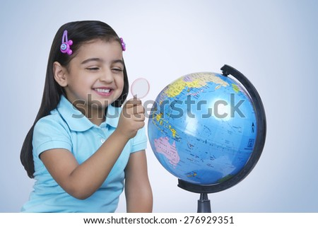 Cheerful girl exploring globe with magnifying glass against blue background