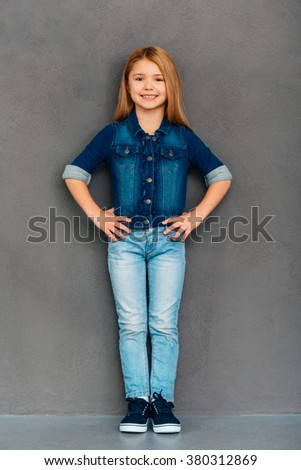 Cheerful girl. Full length of cheerful little girl holding hands on hips and looking at camera with smile while standing against grey background - stock photo