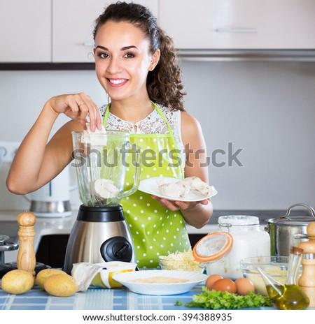 Cheerful girl grinding pate ingredients in blender indoors - stock photo