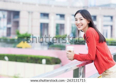 cheerful girl holding a coffee cup, beautiful chinese woman. - stock photo