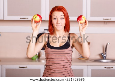 Cheerful girl holding a red apple. Laughter and joy, smile on the face of the woman. Diet, healthy, nutrition, fruits, youth, beauty - concept illustrations for the lifestyle of a modern urban women. - stock photo
