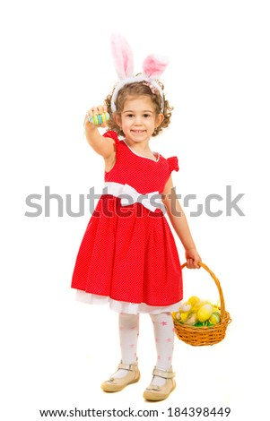 Cheerful girl holding Easter basket with eggs and giving one  colorful egg isolated on white backgorund - stock photo