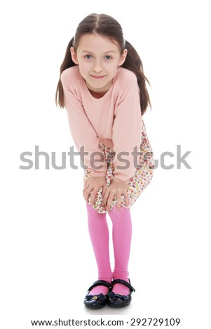 Cheerful girl in a dress and pink cardigan liked put his hands on his knees - isolated on white background - stock photo