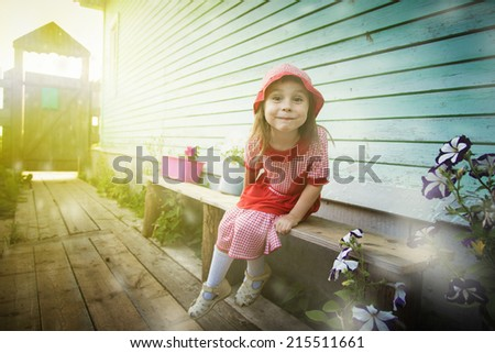 Cheerful girl in a red cap sits on the bench. - stock photo