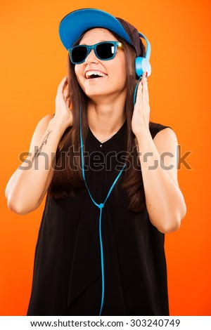 Cheerful girl, in black blouse, blue cap and sunglasses, listening to music with blue headphones - isolated on orange background - stock photo