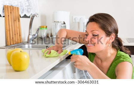 Cheerful girl in green cleaning furniture in kitchen at home