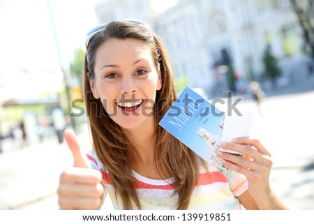 Cheerful girl in Madrid holding city guide and tousist pass - stock photo