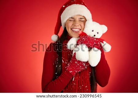 Cheerful girl in Santa cap expressing affection to white teddy bear - stock photo