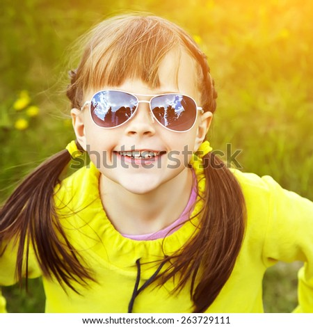 cheerful girl in sunglasses in the park. children outdoors. vacation in the summer park - stock photo