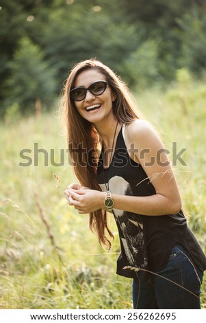 cheerful girl in sunglasses on the nature - stock photo