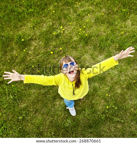 cheerful girl in sunglasses standing on the grass in the park. child outdoors. vacation in the summer park. top view - stock photo