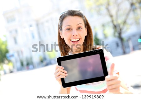 Cheerful girl in town showing tablet screen - stock photo