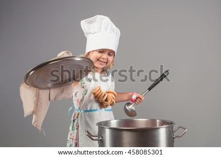 Cheerful girl in uniform chef opens the lid of the pan. The child in the kitchen preparing delicious food. - stock photo