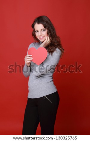 Cheerful girl in warm clothes with red hearts for a greeting card - stock photo