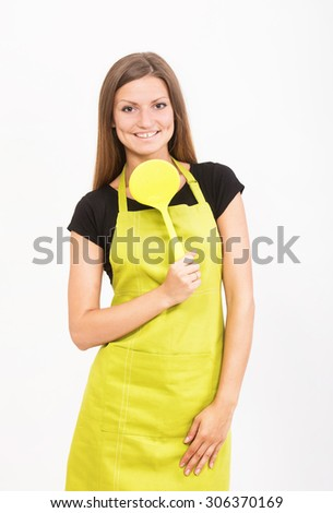 Cheerful girl in yellow apron with a spatula - stock photo