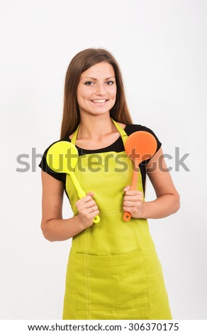 Cheerful girl in yellow apron with two spatulas - stock photo