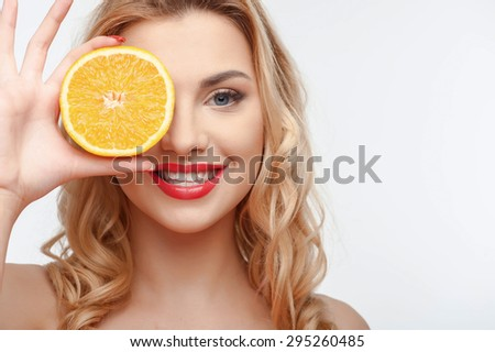 Cheerful girl is covering her eye with orange. She is smiling with enjoyment. Isolated on background and there is copy space in right side - stock photo