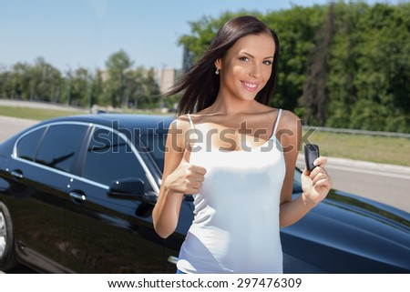 Cheerful girl is giving thumbs up and smiling. She is standing near her new car and holding the showing a key of it. The lady is looking at the camera with happiness - stock photo